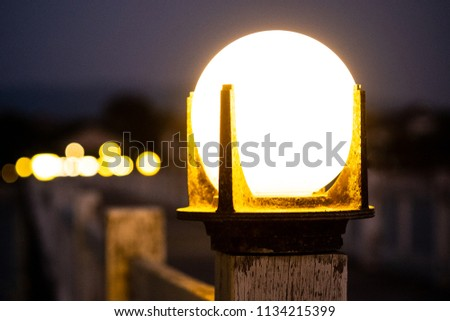 Stock Photo Close up of vintage bollard lamp on wooden railing with bokeh background in night time, selective focus.