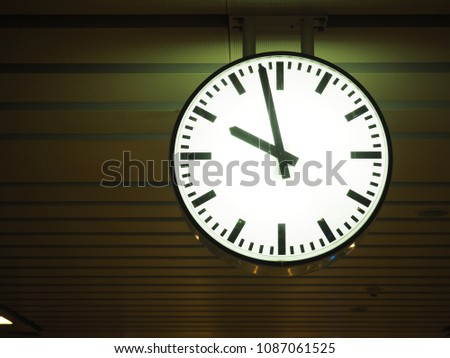 Close up of vintage Clock hanging from the ceiling at subway train station. Clock in train station with copy space for text. Dark light.