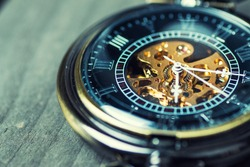 Close up of vintage pocket watch on wooden background