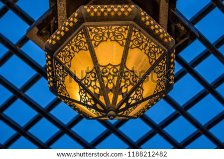 Close up of Vintage style hanging lamp against dark blue sky #1188212482
