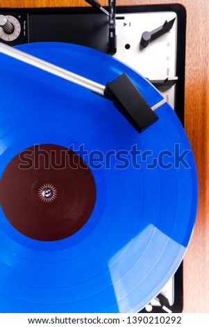 Close up of vintage turntable with a blue vinyl. Wooden plinth. Retro audio equipment.