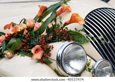 Close-up of Vintage Wedding Car Decorated with Flowers - stock photo