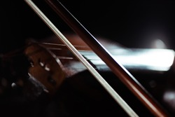 close up of violin and bow in dark, selective focus