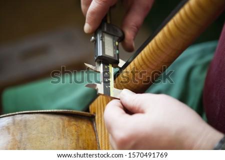 Close-up of violin maker measuring