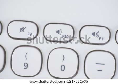 Close-up of Volume Shortcut keys of a white keyboard. Mute, volume down and volume up. #1217582635