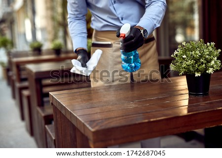Close-up of waiter cleaning tables at outdoor cafe after reopening.