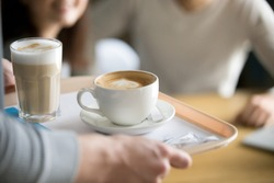 Close up of waiter holding aromatic cappuccino and latte on tray bringing order to café guests, coffeeshop worker give hot drinks to visitors, cups with delicious fresh brewed coffee on platter