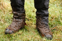 Close up of walking boots. Man, male hiker wearing muddy hiking boots and waterproof gaiters in Wales, UK