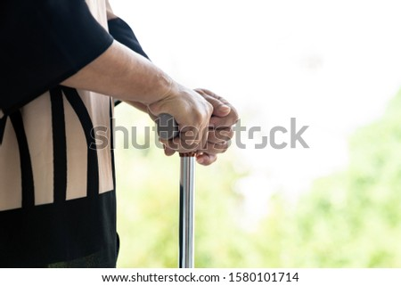 Close up of walking stick or walking cane staff using by elderly senior female hand in domestic living room - recovery and rehabilitation concept