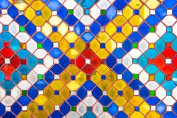 Close up of wall is decorated with stained glass small plate Traditional Thai mosaic art on the wall of temple.