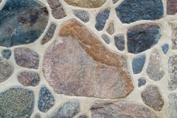 Close-up of wall. Stone and cement. Fragment of a colored, textured stonewall. Bright background. Copy space, place for text