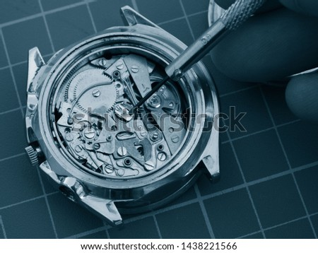 close up of watchmaker repairing old mechanical watch mechanism taking small gear with screwdriver   #1438221566