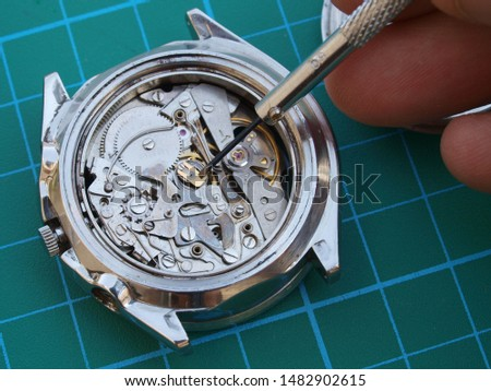 close up of watchmaker repairing old mechanical watch mechanism taking small gear with screwdriver