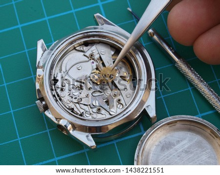 close up of watchmaker repairing old mechanical watch mechanism taking small gear with tweezers #1438221551