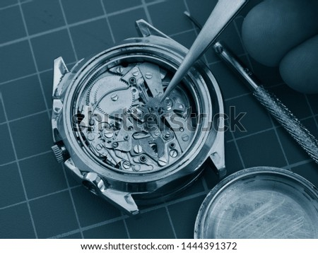close up of watchmaker repairing old mechanical watch mechanism taking small gear with tweezers