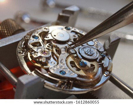 close up of watchmaker repairing old mechanical watch mechanism taking small pivot with tweezers