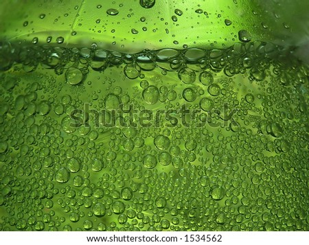 Close-up of water bottle with sparkling drops and a green impression