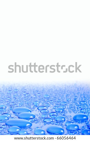 Close up of water drops in blue with shallow depth of field and blank white space for text