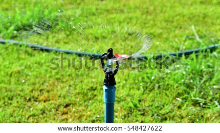 close up of water springer and green field background in garden #548427622