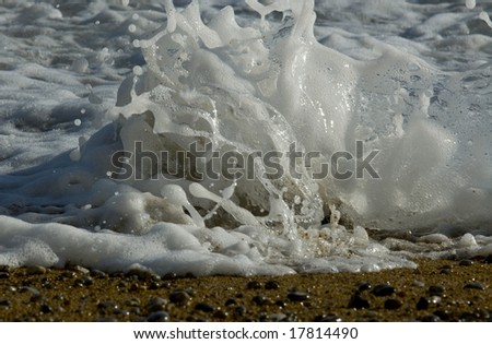 Close up of wave breaking over rock on fore shore