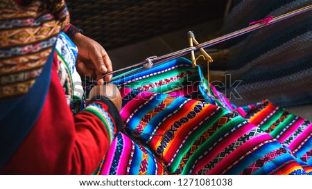 Close up of weaving in Peru. Cusco, Peru   woman dressed in colorful traditional native Peruvian closing knitting a carpet with national pattern. Classic Blue Color of the year 2020 concept.