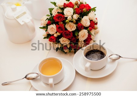 Close up of wedding bouquet with a cup of tea and coffee