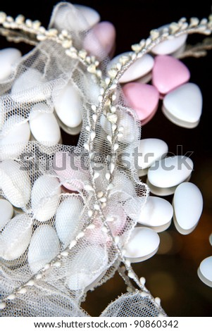 close-up of wedding crowns and almond sweets cover with veil