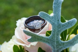 Close up of wedding rings resting on bridal bouquet view through greenery bokeh effect Background outdoors grass