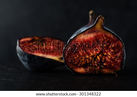 Close up of well ripened figs, cut open to expose seeds and juicy innards.  Still life composition on black slate with black background.