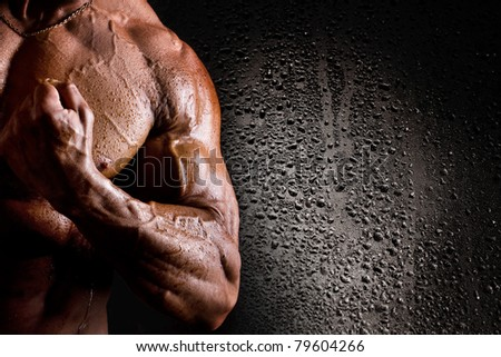 Close-up of wet athletic torso and arm on black background with water drops