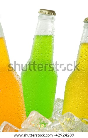 Close up of wet bottles of tropical beverage in different colors - stock photo