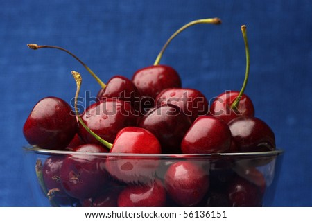 Close-up of wet cherries in glass bowl on dark blue background.