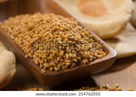 Close up of wheat grains in wooden bowl. Cooked flat bread is in background. #254762050