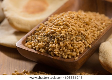 Close up of wheat grains in wooden bowl. Cooked flat bread is in background. #608886248