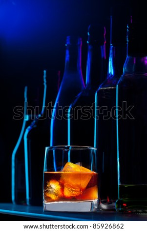 Close-up of whiskey drink and bottles standing on the bar