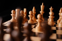 Close up of white and black chess pieces on board. Selective focus on first move of white pawn on chessboard. Concept of intelligent, logical and strategic game