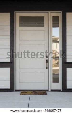 Close Up of White And Black Front Entryway with White Siding, a White Front Door, and Black Framing