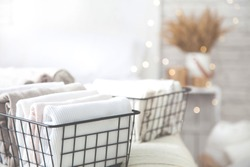 Close-up of white clothes and linen neatly folded in mesh metal containers in bedroom on background of blurred bed. Concept of the perfect organization. Advertising space