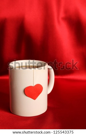 Close-up of white cup of tea and a label in the form of heart
