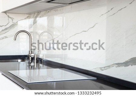 Close up of white glossy kitchen with black quartz countertop and marble tile backsplash. Build-in hidden incorporated hood and undermounted sink.  #1333232495