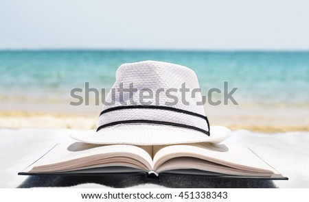 Close up of white hat and open book on the beach towel as summertime concept. Summertime concept #451338343