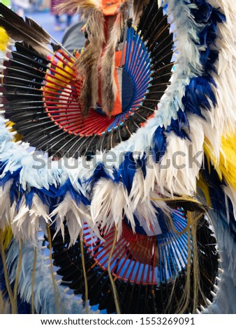 Close up of white, light blue and royal blue feathered headdress and bustle worn by a Native American fancy dancer at a pow wow. #1553269091