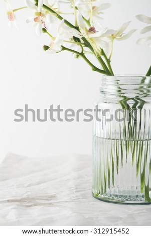 Close up of white orchids flowers in a vintage glass vase #312915452