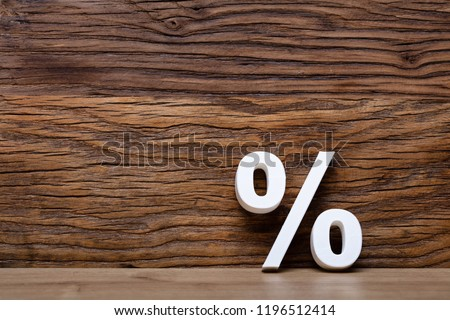 Close-up Of White Percentage Sign Leaning On Wooden Wall