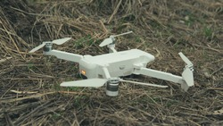 Close-up of white quadrocopter on ground in grass. Modern drone unmanned aerial vehicle with propellers.
