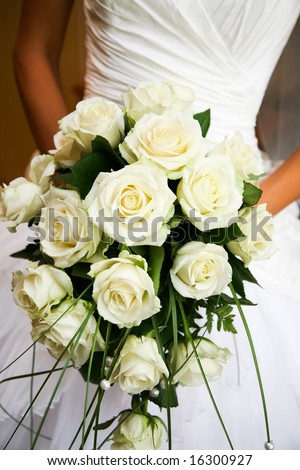 Close-up of white rose bouquet decorated with pearl beads in brideâ??s hands