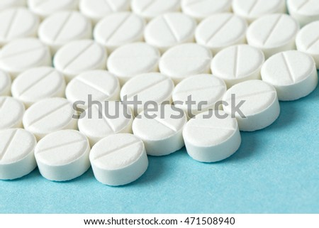Close up of white round tablets on blue background
