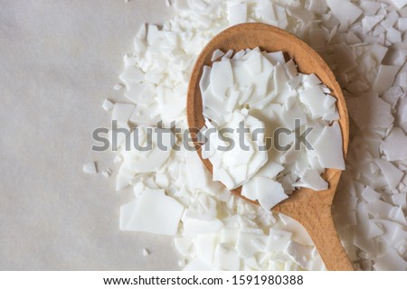 Close up of white soy wax flakes for candle making. Light texture of soy wax flakes. Ingredient for homemade candles. Ecological lifestyle
