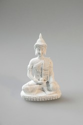Close-up of white statue of Amitabha (Amida or Amitayus),  is a celestial Buddha according to the scripture of Mahayana Buddhism. Isolated statuette on grey pattern background.