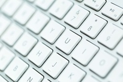 Close up of white wireless aluminum keyboard photographed with shallow depth of field.